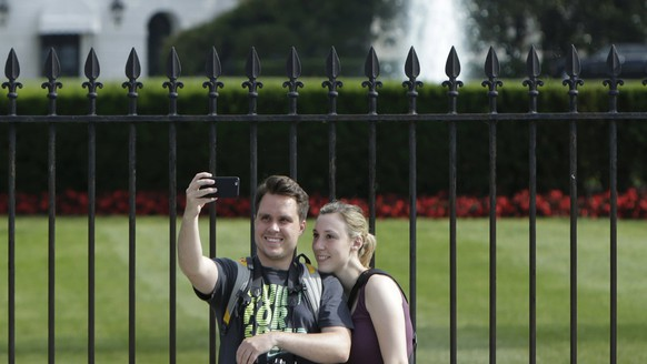 Tourists take selfies by the original South Lawn security fencing at the White House in Washington May 28, 2015. Anti-climb spikes will be added to the fence in late July in an attempt to quell fence jumpers at the Executive Mansion in Washington.   REUTERS/Gary Cameron