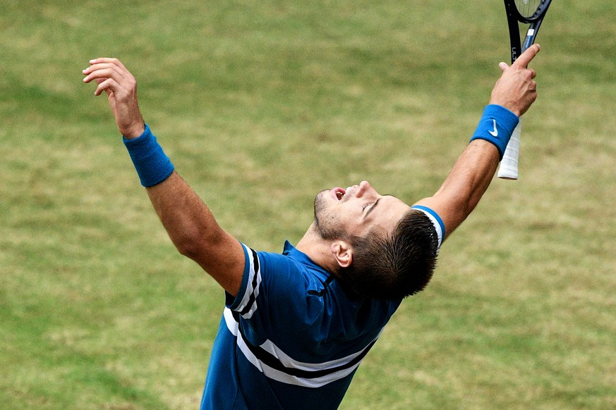 epa06835957 Borna Coric from Croatia celebrates after defeating Roger Federer from Switzerland in the final match of the ATP Tennis Tournament Gerry Weber Open in Halle (Westphalia), Germany, 24 June 2018.  EPA/SASCHA STEINBACH