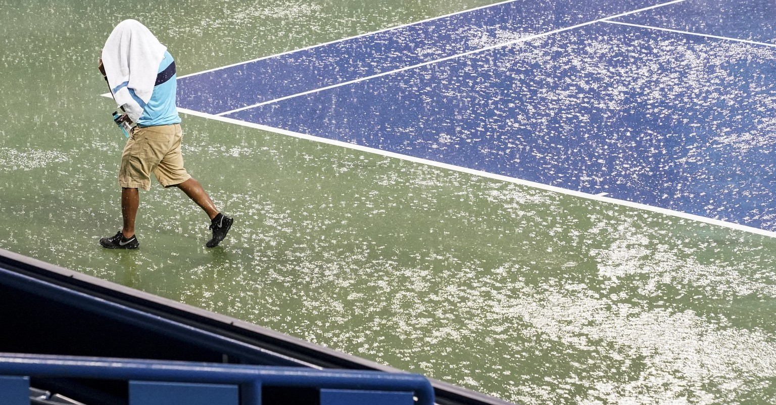 A court attendant moves toward shelter after play was suspended due to rain at the Western & Southern Open tennis tournament Thursday, Aug. 16, 2018, in Mason, Ohio. (AP Photo/John Minchillo)