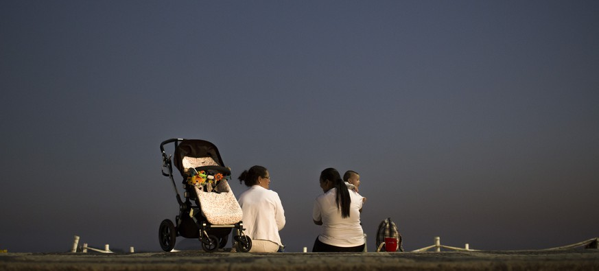 In this Aug. 7, 2014 photo, two nannies chat as they take care of a baby at Leblon beach in Rio de Janeiro, Brazil. A new law fining employers who fail to register their domestic workers is the Brazilian government's latest effort to extend the country's generous labor laws to its around 6 million maids, nannies and other home-care providers. The full impact of the law is hard to measure because informal work is not reported to the government, but experts estimate about 300,000 domestic workers have lost their jobs as a result of the legislation. (AP Photo/Felipe Dana)