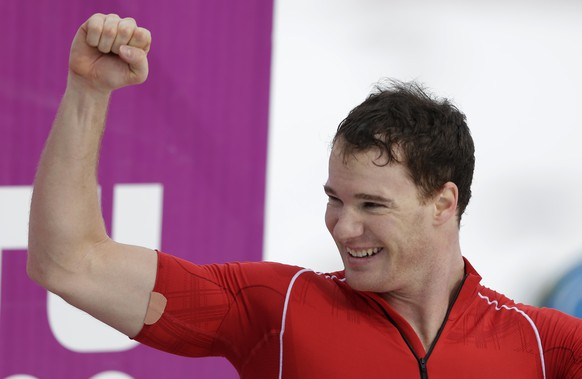 Switzerland's Dario Cologna celebrates after the men's 15K classical-style cross-country race at the 2014 Winter Olympics, Friday, Feb. 14, 2014, in Krasnaya Polyana, Russia. (AP Photo/Matthias Schrader)