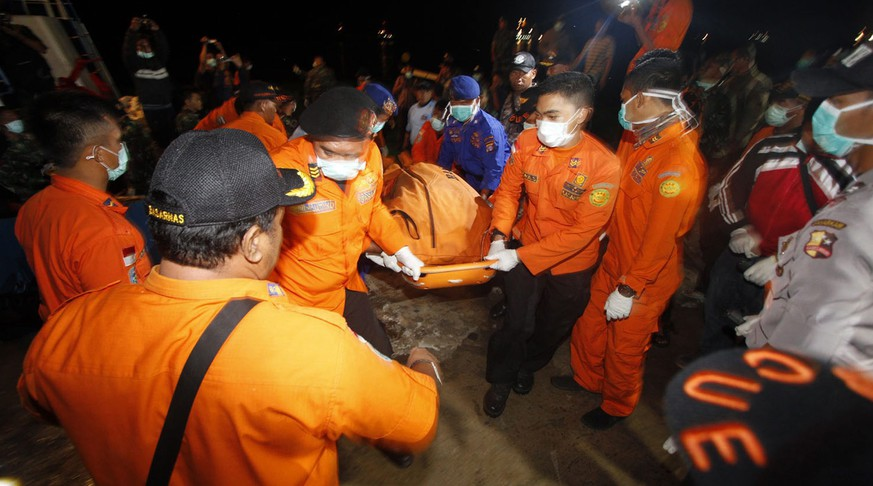 epa04543940 A picture made available on 01 January 2015 shows Indonesian rescuers carrying the body of a victim of the crashed AirAsia from a boat at Panglima Utar port in Kumai, Central Borneo, Indonesia, 31 December 2014. Indonesian rescuers retrieved three more bodies from the sea on 31 December but the search to recover more victims from the AirAsia plane crash was hampered by bad weather, the recue chief said. AirAsia Indonesia flight QZ8501 crashed into the Java Sea on 28 December, about halfway through a two-hour flight between Surabaya, Indonesia's second largest city, and Singapore.  EPA/TEGUH ABADI