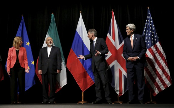 British Foreign Secretary Philip Hammond (2nd R), U.S. Secretary of State John Kerry (R) and European Union High Representative for Foreign Affairs and Security Policy Federica Mogherini  (L) talk to Iranian Foreign Minister Mohammad Javad Zarif as the wait for Russian Foreign Minister Sergey Lavrov (not pictured) for a group picture at the Vienna International Center in Vienna, Austria July 14, 2015. Iran and six major world powers reached a nuclear deal on Tuesday, capping more than a decade of on-off negotiations with an agreement that could potentially transform the Middle East, and which Israel called an