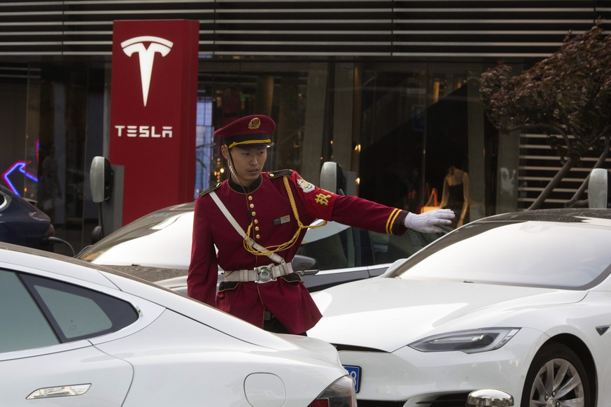 A security guard directs traffic near a Tesla charging station in Beijing, China, Tuesday, May 22, 2018. China said Tuesday it will reduce auto import duties effective July 1 following pledges to buy more U.S. goods and end restrictions on foreign ownership in the industry. (AP Photo/Ng Han Guan)