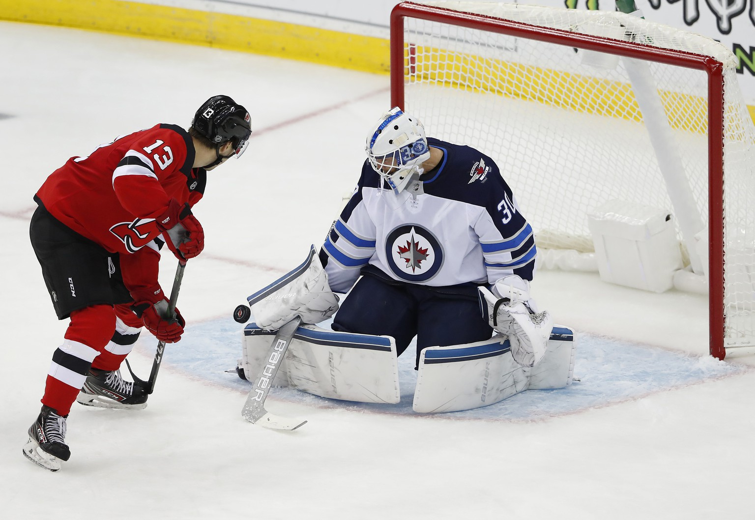 Winnipeg Jets goaltender Laurent Brossoit (30) makes a save against New Jersey Devils center Nico Hischier (13) during the third period of an NHL hockey game Friday, Oct. 4, 2019, in Newark, N.J. (AP Photo/Noah K. Murray)