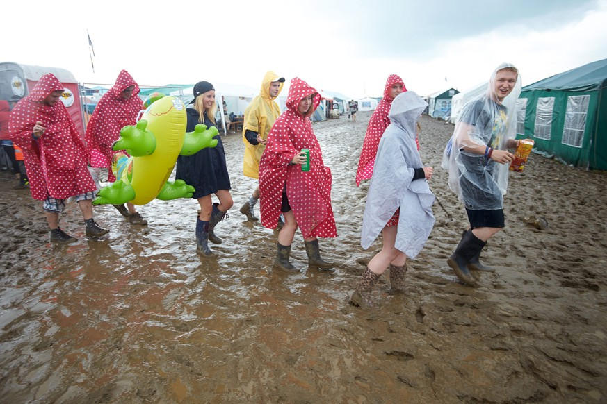 epa05344333 Rock fans from Solingen walking across the muddy camping area at the music festival 'Rock am Ring' in Mendig, Germany, 03 June 2016. The event originally took place at the Nuerburgring circuit before it closed its doors in 2014. The 31th edition of the festival takes place on a former military airfield in Mendig from 03 to 05 June.  EPA/THOMAS FREY