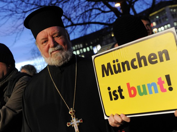 epa04557261 Orthodox Archpriest Apostolos Malamoussis holds a sign bears the event title 'Munich is colorful' at a demonstration in Munich, Germany, 12 January 2015. The demonstration is turned against a rally by the anti-Islam association 'Bagida' (Bavaria against the Islamization of the west).  EPA/TOBIAS HASE