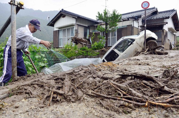 A man clears debris at an area affected by landslide caused by heavy rains due to Typhoon Neoguri in Nagiso town, Nagano prefecture, in this photo taken by Kyodo July 10, 2014. A landslide pummelled the town of Nagiso in central Japan late on Wednesday, sending a cascade of mud and boulders through the streets and killing a 12-year-old boy, bringing the death toll from the storm to three. Mandatory credit. REUTERS/Kyodo (JAPAN - Tags: ENVIRONMENT DISASTER) ATTENTION EDITORS - FOR EDITORIAL USE ONLY. NOT FOR SALE FOR MARKETING OR ADVERTISING CAMPAIGNS. THIS IMAGE HAS BEEN SUPPLIED BY A THIRD PARTY. IT IS DISTRIBUTED, EXACTLY AS RECEIVED BY REUTERS, AS A SERVICE TO CLIENTS. MANDATORY CREDIT. JAPAN OUT. NO COMMERCIAL OR EDITORIAL SALES IN JAPAN. YES
