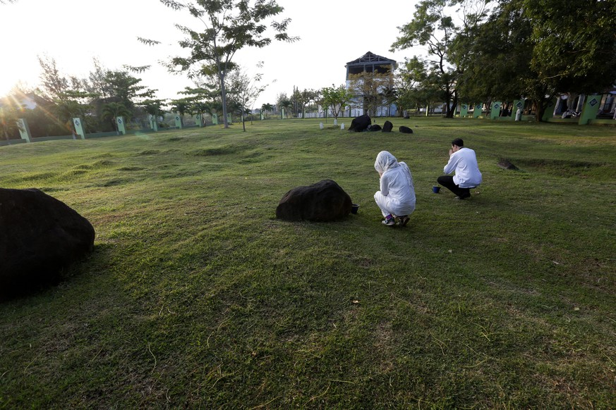 epa05081055 A general view shows people praying as they visit the Ulee Lheue mass grave during the 11th anniversary of the 2004 Indian Ocean Tsunami, or Boxing Day tsunami, in Banda Aceh, Aceh Province, Indonesia, 26 December 2015. December 2015 marks the eleventh anniversary of the Indian Ocean Tsunami which struck on 26 December 2004 triggered by a 9.2 earthquake in the Indian Ocean off the west coast of northern Sumatra, Indonesia, killing an estimated 230,000 people in 13 countries along the ocean.  EPA/HOTLI SIMANJUNTAK