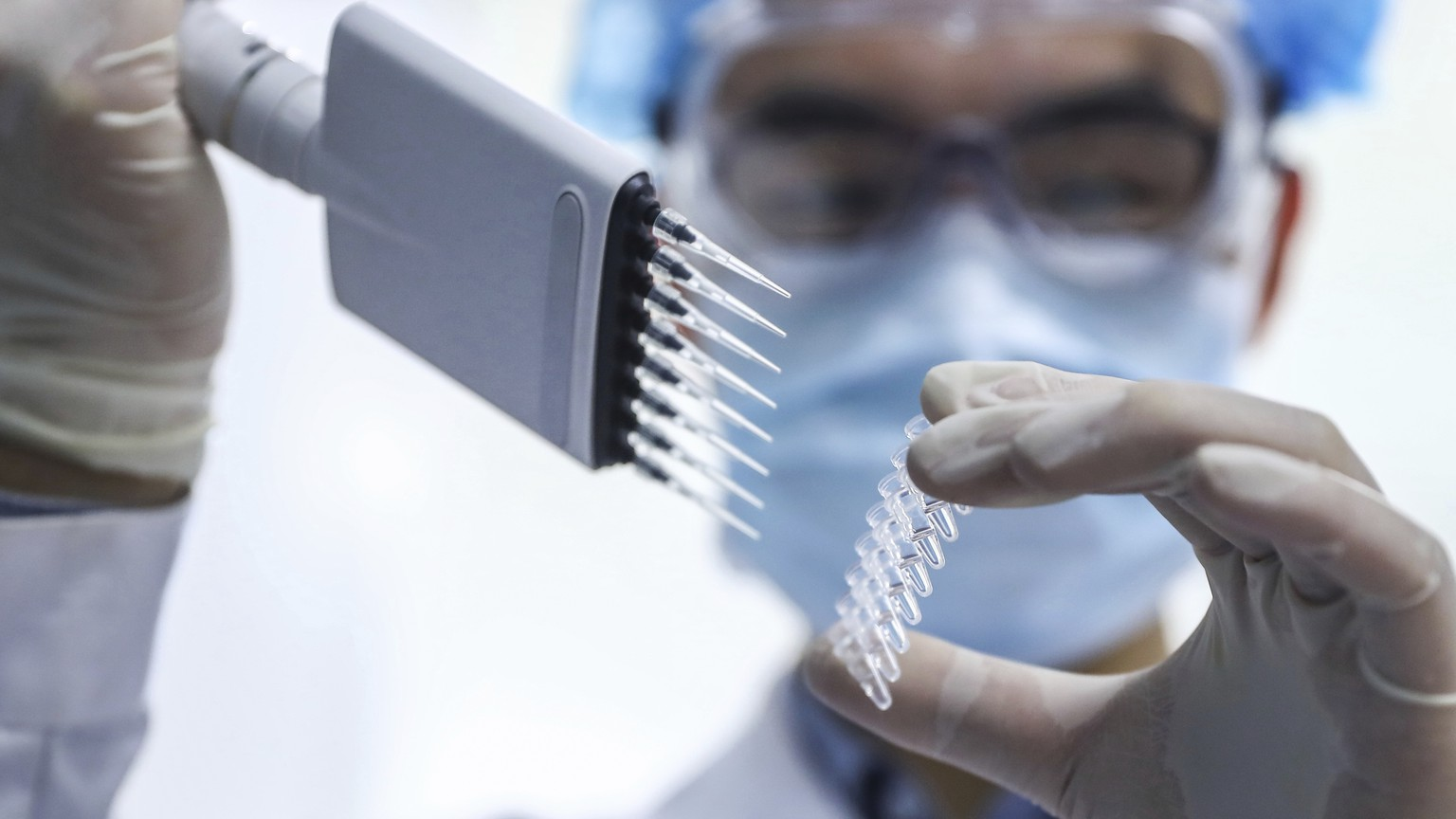 In this April 11, 2020 photo, released by Xinhua News Agency, a staff member tests samples of a potential COVID-19 vaccine at a production plant of SinoPharm in Beijing. In the global race to make a coronavirus vaccine, the state-owned Chinese company is boasting that it gave its employees, including top executives, experimental shots even before the government OK'd testing in people. (Zhang Yuwei/Xinhua via AP)