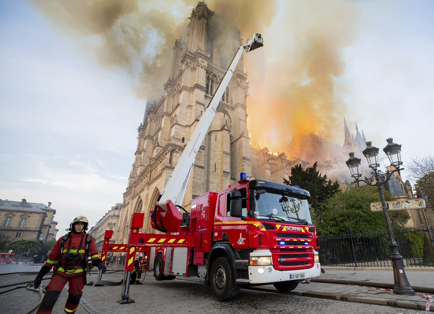 This photo provided on Tuesday April 16, 2019 by the Paris Fire Brigade shows fire fighters working at the burning Notre Dame cathedral, Monday April 15, 2019. Experts assessed the blackened shell of Paris' iconic Notre Dame Tuesday morning to establish next steps to save what remains after a devastating fire destroyed much of the cathedral that had survived almost 900 years of history. (Benoit Moser, BSPP via AP)