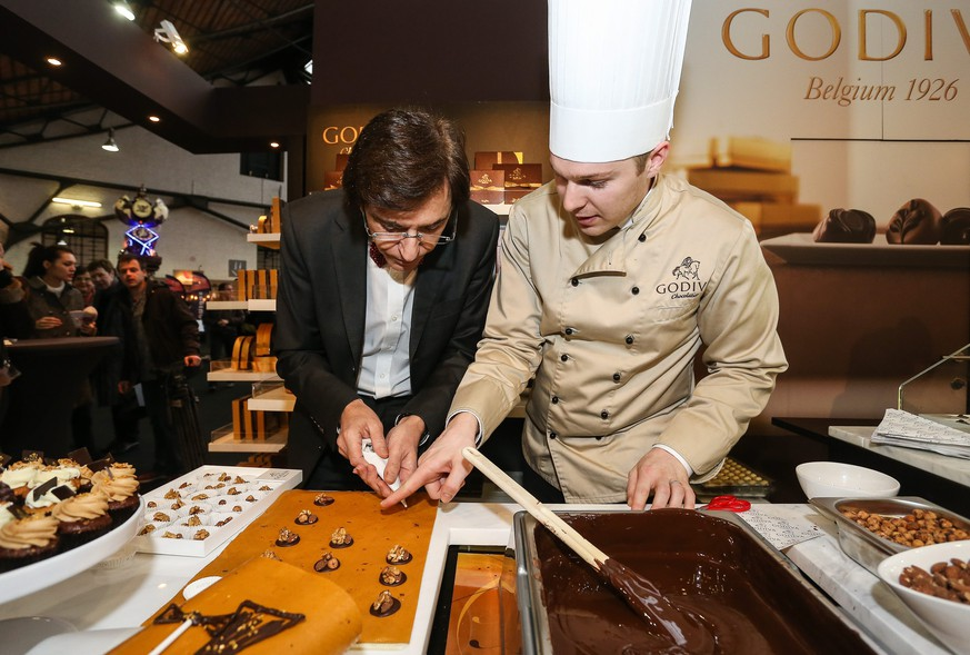 epa04059856 Belgian Prime Minister Elio Di Rupo (L) at chocolate manufacturer Godiva during a visit to the Chocolate fair, in Brussels, Belgium, 07 February 2014. The 20th Chocolate fair runs from 07 till 09 February 2014.  EPA/JULIEN WARNAND