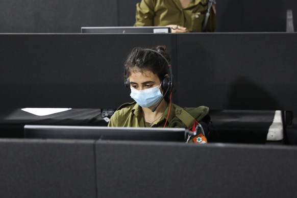 epa08729066 Israeli soldiers in the central national control room Headquarters of the Home Front Command dealing with the coronavirus COVID-19 in the city of Ramla near Tel Aviv, 08 October 2020. The Israeli Ministry of Defense, in cooperation with the Israeli army, is deploying more than 5,000 soldiers to assist the state effort in the national struggle to prevent the spread of the corona virus, with a large set of tracking and detection of virus infections and mass array of epidemiological tests. Israel is on a three weeks national lockdown during the holiday period.  EPA/ABIR SULTAN