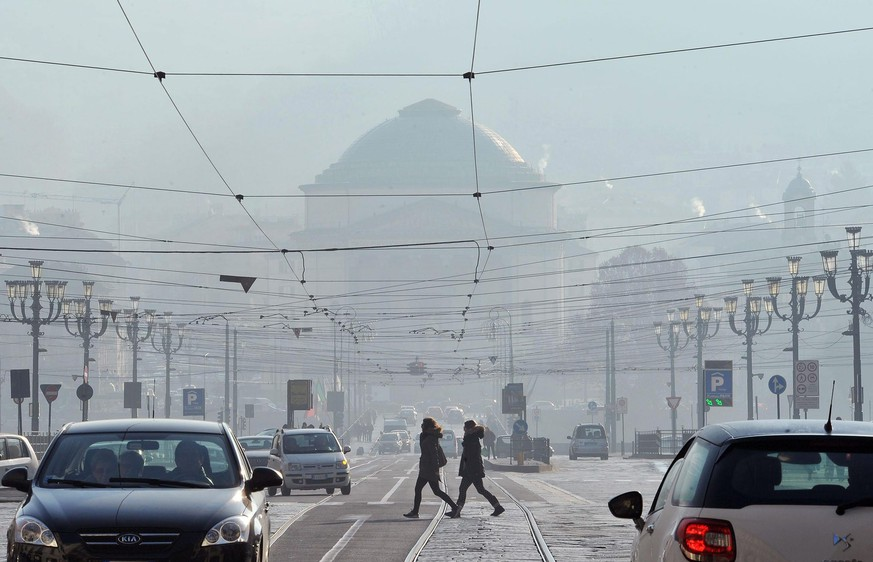 epa05075339 People walk in the streets of polluted Turin, Italy, 19 December 2015. The legal limit of pollution is 35 days per year  with more than 50 micrograms per cubic metre of PM10. Turin is expected to reach 73 days over the limit, Italian environmentalist association Legambiente said.  EPA/ALESSANDRO DI MARCO