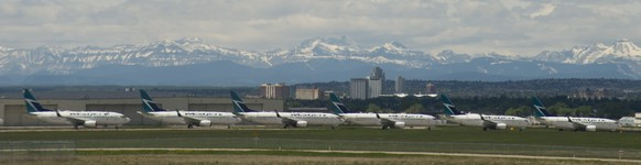 A line of parked WestJet planes are seen on the tarmac of Calgary International Airport in Calgary, Tuesday, June 9, 2020. Airlines in Canada and around the world are suffering financially due to the lack of travel and travel bans due to COVID-19. (Jonathan Hayward/The Canadian Press via AP)