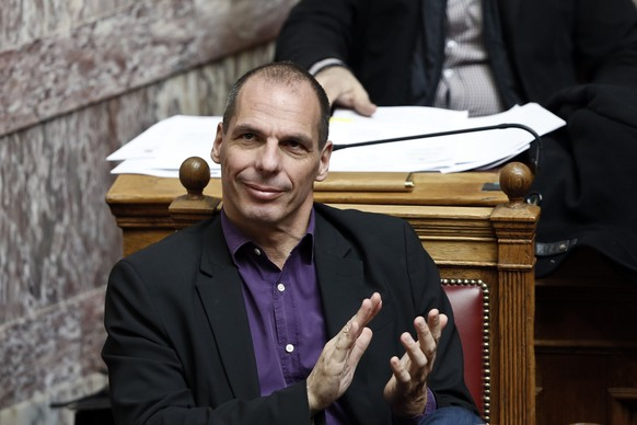 Greek Finance Minister Yanis Varoufakis applauds during a parliamentary session in Athens March 18, 2015. With incendiary interviews, an undiplomatic demeanour, a celebrity photo shoot and an obscene finger gesture, Varoufakis is becoming part of Greece's debt problem rather than the solution, or so his euro zone partners believe. Many Greeks regard their new finance minister as a breath of fresh air, a man who has told his colleagues in the Eurogroup a few home truths about the futility of forcing austerity policies on an economy that has endured a depression for five years. But his readiness to break the conventions of European discourse has caused consternation, and not just among the buttoned-up finance chiefs and bureaucrats who populate the Eurogroup.  REUTERS/Alkis Konstantinidis  (GREECE - Tags: POLITICS BUSINESS)