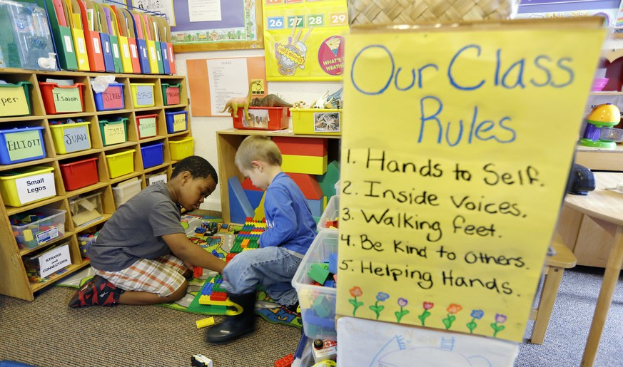 Isaiah Simanton, 5, left, and Elliott Hill, 4, right, play with Legos next to a poster of class rules in a Pre-Kindergarten class at the Community Day Center for Children, during class Tuesday, Oct. 21, 2014, in Seattle. Two Seattle ballot proposals that could both benefit thousands of preschool children are competing against each other for votes in the upcoming November election. (AP Photo/Ted S. Warren)