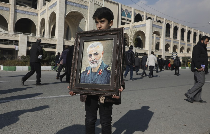 A boy carries a portrait of Iranian Revolutionary Guard Gen. Qassem Soleimani, who was killed in the U.S. airstrike in Iraq, prior to the Friday prayers in Tehran, Iran, Friday Jan. 3, 2020. Iran has vowed