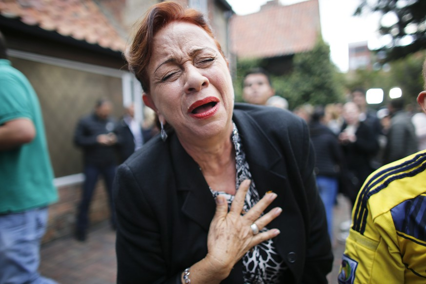 An opponent to the peace deal signed between the Colombian government and rebels of the Revolutionary Armed Forces of Colombia, FARC, celebrates after she listened to the results of the referendum to decide whether or not to support a peace accord to in Bogota, Colombia, Sunday, Oct. 2, 2016. Colombia's peace deal with leftist rebels was on the verge of collapsing in a national referendum, with those opposing the deal leading by a razor-thin margin with almost all votes counted (AP Photo/Ariana Cubillos)