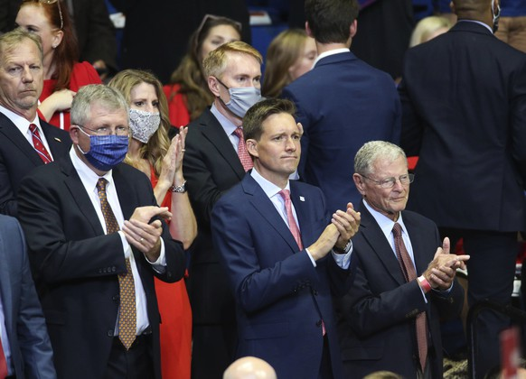 Government officials, including U.S. Reps. Kevin Hern, top left, and Frank Lucas, left, Lt. Gov. Matt Pinnell, center, and U.S. Sens. James Lankford, top, and Jim Inhofe applaud before a campaign rally for President Donald Trump at the BOK Center in downtown Tulsa, Okla., Saturday, June 20, 2020. (Matt Barnard/Tulsa World via AP)