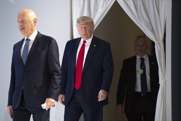 US President Donald Trump, center, and German Klaus Schwab, left, Founder and Executive Chairman of the World Economic Forum, WEF, arrives on stage before addressing a plenary session during to the 50th annual meeting of the World Economic Forum, WEF, in Davos, Switzerland, Tuesday, January 21, 2020. The meeting brings together entrepreneurs, scientists, corporate and political leaders in Davos from January 21 to 24. (KEYSTONE/Gian Ehrenzeller)