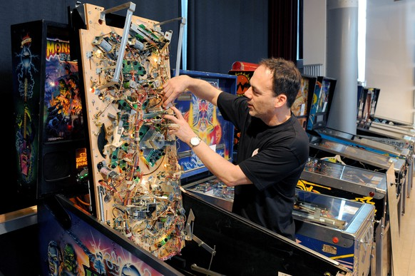 epa04796616 Stefan Schuelke makes adjustments to a machine before the German Pinball Championships at the Musical-Theater in Bremen, Germany, 13 June 2015.  EPA/INGO WAGNER