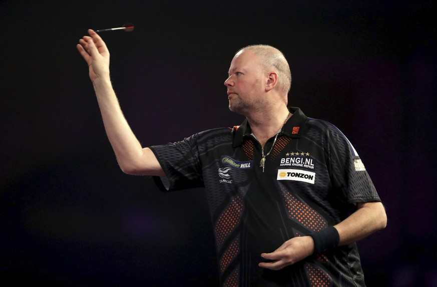 Raymond van Barneveld of the Netherlands throws a dart during his quarterfinal match against fellow countryman Michael van Gerwen on day thirteen of the World Darts Championship at Alexandra Palace, London, Friday Dec. 29, 2017. (Adam Davy/PA via AP)