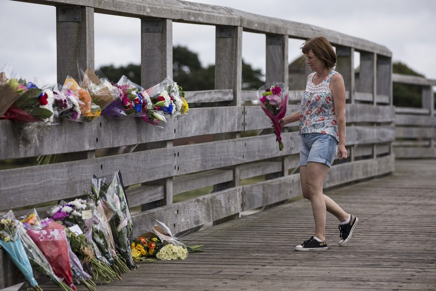 SHOREHAM, ENGLAND - AUGUST 23:  A woman lays flowers near the site where a Hawker Hunter fighter jet crashed on August 23, 2015 in Shoreham, England. The aircraft came down while performing at the Shoreham Airshow yesterday, killing at least seven people. The pilot is said to be in a critical condition in hospital.  (Photo by Dan Kitwood/Getty Images)