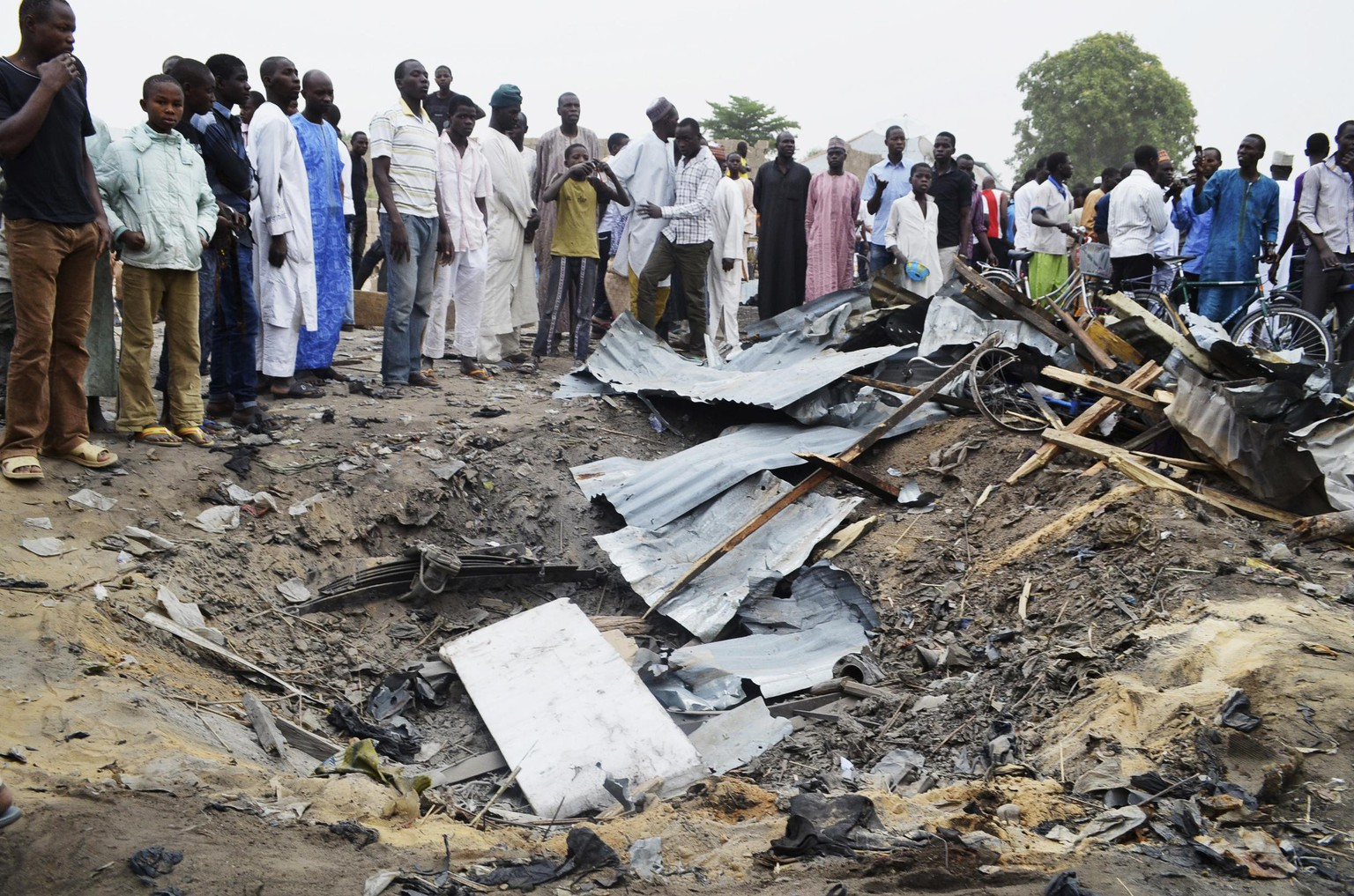 People gather around a crater created after an explosion of one of two vehicles laden with explosives in Ajilari-Gomari near the city's airport, in Maiduguri March 2, 2014. At least 10 people were killed after a bomb went off at around 6 p.m. (1700 GMT) on Saturday in a busy market area in Ajilari-Gomari, in Maiduguri, witnesses and a police source said, in a region where the Islamist sect Boko Haram is pursuing a bloody insurgency. The final death toll was likely to be higher because dozens of people were trapped in the rubble, the witnesses said. REUTERS/Stringer (NIGERIA - Tags: CIVIL UNREST POLITICS)