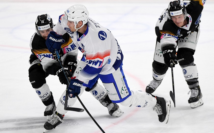Lugano's player Mark Arcobello, ZSC's player Pius Suter, and Lugano's player Daniel Carr, from left, fight for the puck, during the 1/8 final game of Swiss Cup 2020/21 between HC Lugano and ZSC Lions, at the Corner Arena stadium in Lugano, on Saturday, November 07, 2020. (KEYSTONE/Ti-Press/Samuel Golay)