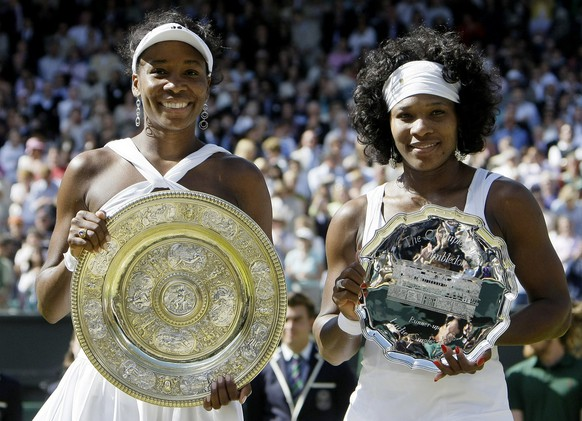 Venus Williams left, of the US holds her trophy after winning the women's singles final against her sister Serena right, on the Centre Court at Wimbledon, Saturday, July 5 , 2008. (AP Photo/Anja Niedringhaus)