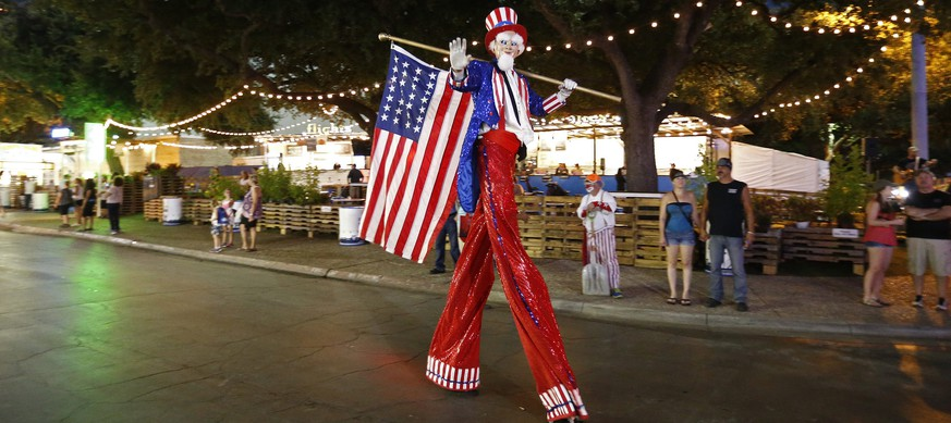 epa05572156 A man on stilts dressed as Uncle Sam walks along during a parade at the State Fair of Texas in Dallas, Texas, USA, 05 October 2016. The annual State Fair of Texas has taken place nearly every year since 1886 and in one of the most popular state fairs in the USA.  EPA/LARRY W. SMITH