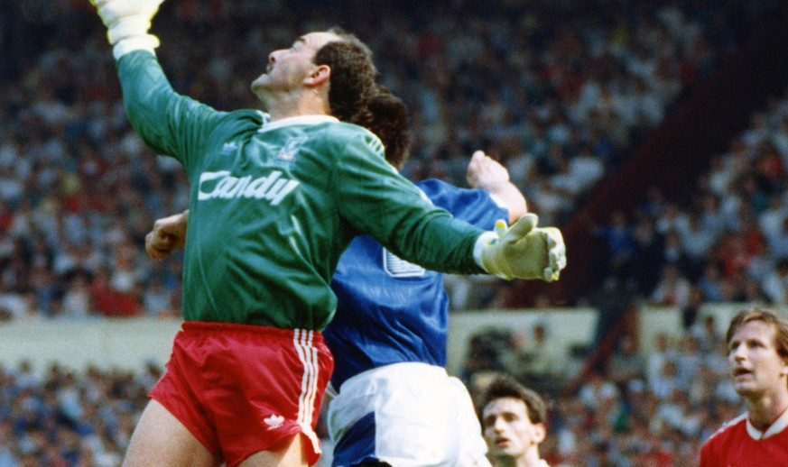 Liverpool's South African-born goalkeeper Bruce Grobbelaar stretches to take the ball away from Everton striker Graeme Sharp during the FA Cup Final, at Wembley Stadium, London, on May 20, 1989. Liverpool's Ronnie Whelan, right, and next to him is Everton's Pat Nevin. Liverpool won the match 3-2. (AP Photo/White)