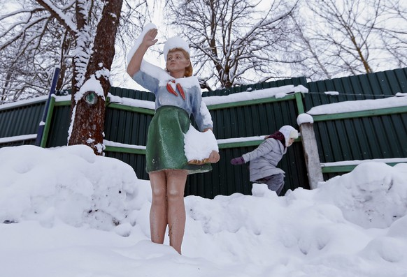 epaselect epa05706890 A child plays near a snow-covered sculpture of a Soviet pioneer at a park in Moscow, Russia, 09 January 2017. Temperatures dropped to minus 24 degrees Celsius in the Russian capital.  EPA/YURI KOCHETKOV