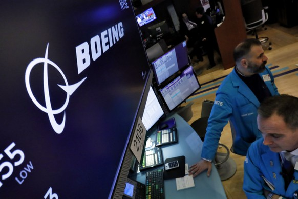 The Boeing logo appears above a trading post on the floor of the New York Stock Exchange, Thursday, March 12, 2020. Boeing stock Boeing Co. closed down $34.24 to $154.84. (AP Photo/Richard Drew)