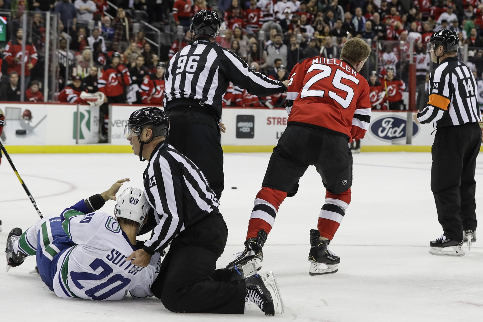 Referee's separate Vancouver Canucks' Brandon Sutter (20) and New Jersey Devils' Mirco Mueller (25) after a fight during the second period of an NHL hockey game Saturday, Oct. 19, 2019, in Newark, N.J. (AP Photo/Frank Franklin II)