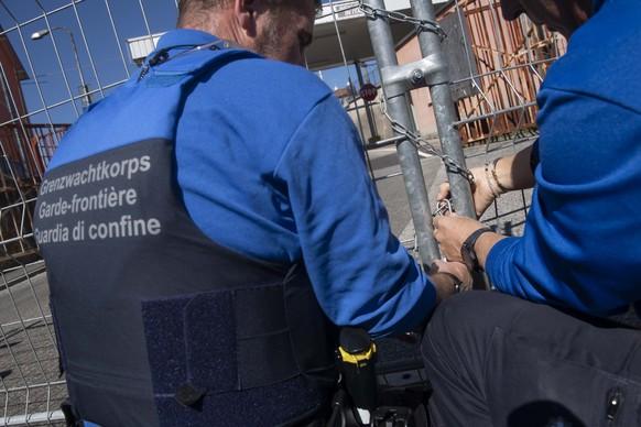 Beamte des Grenzwachkorps schliessen den Grenzuebergang San Pietro di Stabio zwischen der Schweiz und Italien mit Gittern und Ketten, am Mittwoch, 11. Maerz 2020. Ab heute Mittwoch wird im Tessin der Grenzverkehr aus Italien auf die groesseren Grenzuebergaenge kanalisiert, um den Grenzverkehr mit Italien und die Ausbreitung des Coronavirus (Covid-19) besser kontrollieren zu koennen. (KEYSTONE/Ti-Press/Davide Agosta)