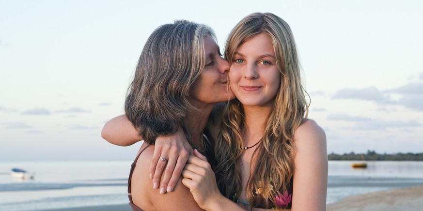 Mother and daughter (14-15) hugging on beach
