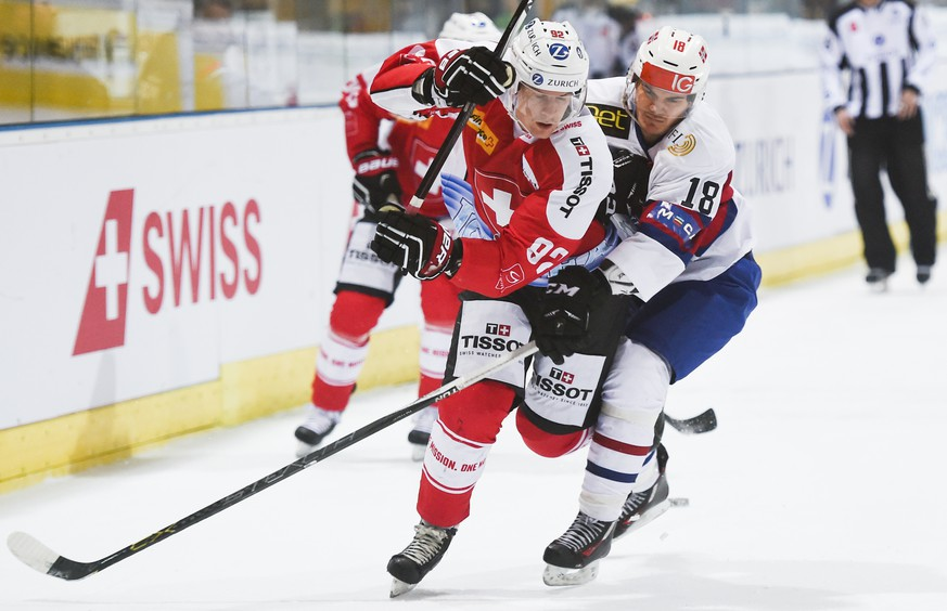 Gaetan Haas of Switzerland, left, fights for the puck with Thomas Valkvae Olsen of Norway, during the semifinals of the Arosa Challenge, on Friday, December 18, 2015, in Arosa, Switzerland. (KEYSTONE/Gian Ehrenzeller)