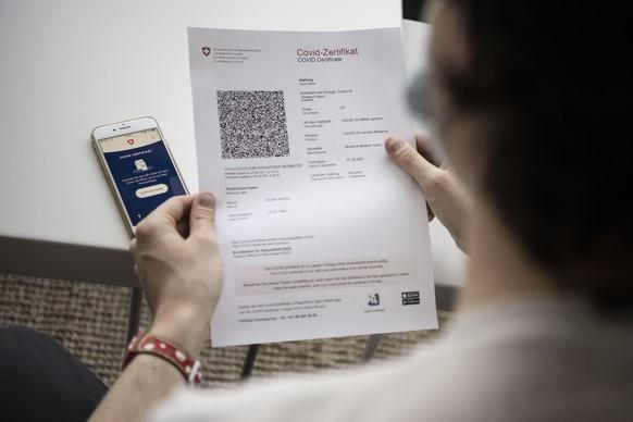 ZUM SCANNEN DES COVID-ZERTIFIKATS MITTELS DER COVID CERTIFICATE APP, STELLEN WIR IHNEN FOLGENDE BILDER ZUR VERFUEGUNG. WEITERE BILDER FINDEN SIE AUF visual.keystone-sda.ch --- Das Covid-Zertifikat Schweiz wird mit einem Mobiltelefon eingescannt, am Dienstag, 15. Juni 2021 in Zuerich. Das Covid-Zertifikat enthaelt neben Name, Vorname, Geburtsdatum und einer Zertifikatsnummer auch die Angaben zur Covid-19-Impfung, zur Genesung oder zum negativen PCR-Test- bzw. Antigen-Schnelltest-Resultat. Der im Covid-Zertifikat angezeigte QR-Code soll das Zertifikat dank einer elektronischen Signatur der Schweizerischen Eidgenossenschaft faelschungssicher machen und die Echtheit des Covid-Zertifikats garantieren. (KEYSTONE/Christian Beutler)