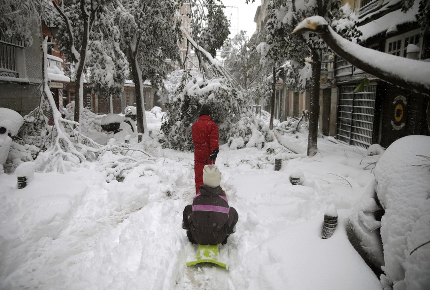 A man walks dragging a sled with a girl along a street with snow and fallen three branches during a heavy snowfall in downtown Madrid, Spain, Saturday, Jan. 9, 2021.  A persistent blizzard has blanketed large parts of Spain with 50-year record levels of snow, halting traffic and leaving thousands trapped in cars or in train stations and airports that suspended all services as the snow kept falling on Saturday. (AP Photo/Andrea Comas)