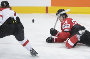 Switzerland's Dean Kukan, right, falls challenging for the puck with Austria's Brian Lebler, left, during the Hockey World Championships Group A match in Prague, Czech Republic, Saturday, May 2, 2015. (AP Photo/Petr David Josek)