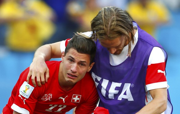 Switzerland's Michael Lang (R) comforts Fabian Schaer after extra time in the 2014 World Cup round of 16 game between Argentina and Switzerland at the Corinthians arena in Sao Paulo July 1, 2014.  REUTERS/Eddie Keogh (BRAZIL  - Tags: TPX IMAGES OF THE DAY SOCCER SPORT WORLD CUP)