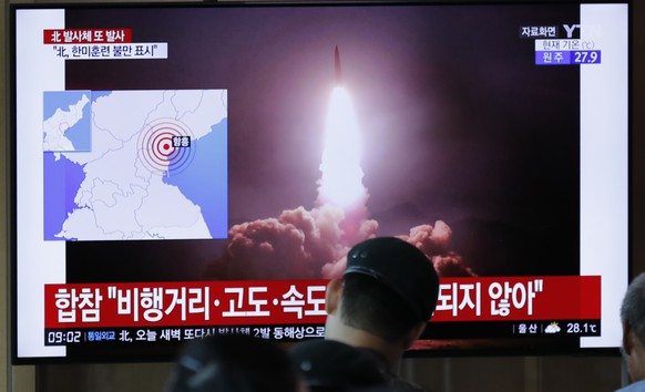 People watch a TV news program reporting about North Korea's firing projectiles with a file image at the Seoul Railway Station in Seoul, South Korea, Saturday, Aug. 10, 2019. North Korea on Saturday extended a recent streak of weapons display by firing projectiles twice into the sea, according to South Korea's military. The letters read on the top