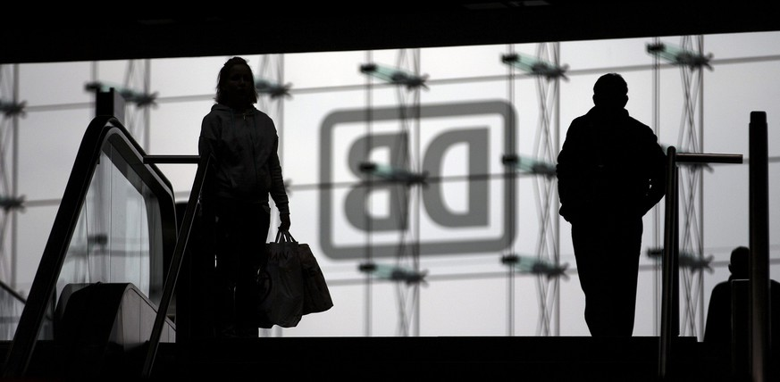 Commuters walk in front of the logo of German rail operator Deutsche Bahn at Berlin's Hauptbahnhof main railway station in Berlin in this October 7, 2014 file photo. Germany's GDL train drivers union GDL, which represents just 20,000 of the railways' 196,000 workers, said November 4, 2014 they would walk off the job on their longest strike in the history of German railway's Deutsche Bahn that will start on Wednesday and run until Monday.      REUTERS/Hannibal Hanschke (GERMANY  - Tags: BUSINESS CIVIL UNREST BUSINESS EMPLOYMENT TRANSPORT)