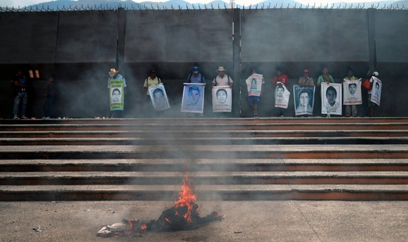 epa04749065 A group of people, who support relatives of the 43 missing Mexican students last seen in Iguala on 26 September 2014, burn electoral propaganda outside the government headquarters in Chilpancingo, Guerrero, Mexico, 14 May 2015. The Mexican state of Guerrero has been seeing a wave of violence prior to the upcoming 07 June elections after the kidnapping of a state legislator on 13 May and the killing of a candidate for the Mayor's Office of Chilapa on 01 May.  EPA/JOSE LUIS DE LA CRUZ