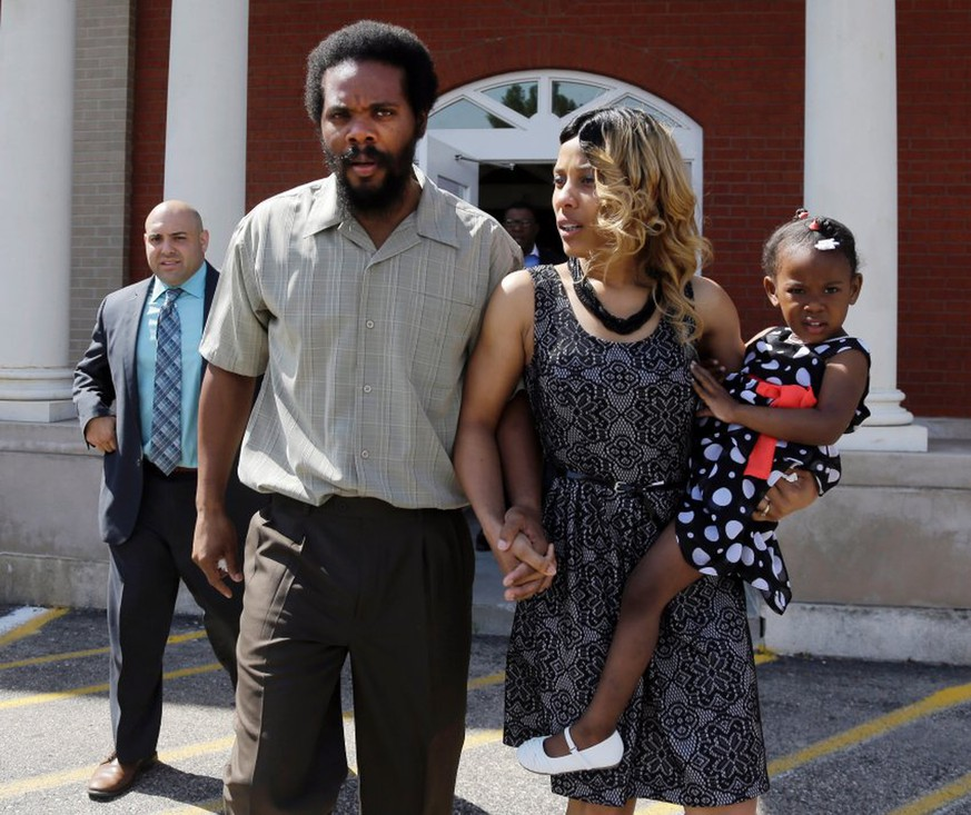 "Cornealious ""Mike"" Anderson walks out of the Mississippi County Courthouse along with his wife, LaQonna Anderson, daughter Nevaeh, 3, and attorney Patrick Megaro, far left, after being released from custody, Monday, May 5, 2014, in Charleston, Mo. A judge ordered the release of Anderson, who was convicted of robbery in 2000 but never sent to prison until a clerical mistake was discovered last year when he was put behind bars. (AP Photo/Jeff Roberson)"