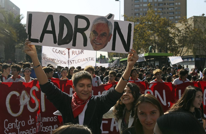 A student holds a banner with the image of President Sebastian Piñera and the word thief written in Spanish, during a protest in Santiago, Chile, on Thursday, April 19, 2018. Thousands of people marched against education for profit and to reject the new government of President Sebastián Piñera. (AP Photo / Luis Hidalgo)