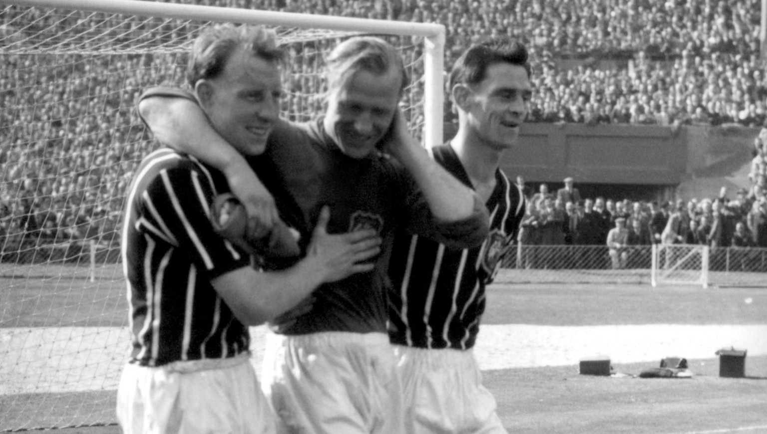 "FILE - A May 5, 1956 photo from files of Bernd Trautmann, more commonly known as Bert, Manchester City's German-born goalkeeper, centre, being assisted from the pitch by two unidentified players, suffering from a broken neck, during the FA Cup final against Birmingham, at London's Wembley Stadium. The German football federation said Friday, July 19, 2013, that Trautmann died in La Llosa, near Valencia, Spain, where he lived. Trautmann's wife Marlies told the federation he died Friday morning. Trautmann had suffered two heart attacks this year but appeared to have recovered well. Manchester City called Trautmann one of the club's ""greatest goalkeepers of all time and a true club legend.""  (AP Photo/PA, File) UNITED KINGDOM OUT  NO SALES  NO ARCHIVE"