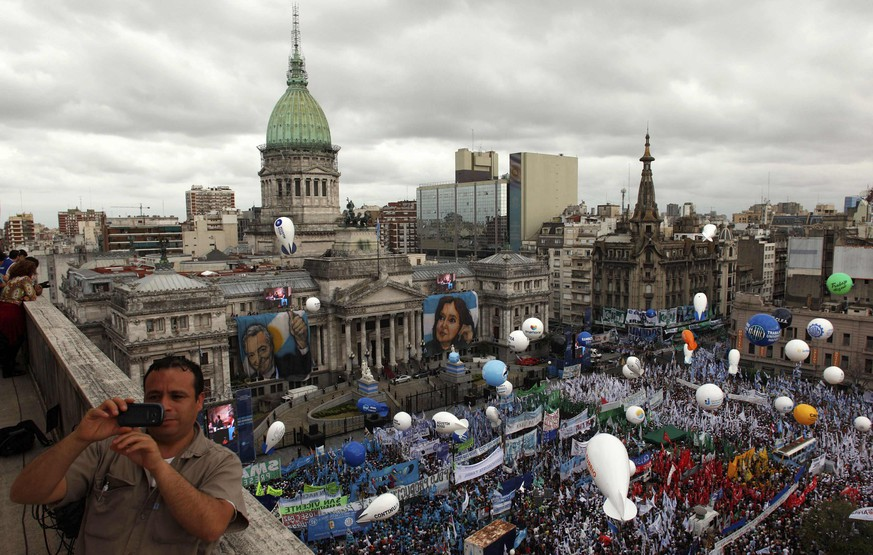 A man takes a selfie with his phone as supporters of Argentina's President Cristina Fernandez de Kirchner gather outside the Argentine Congress during the opening session of the 133rd legislative term of Congress in Buenos Aires, March 1, 2015.  REUTERS/Martin Acosta (ARGENTINA - Tags: POLITICS)